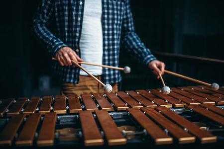 Xylofoon speler handen met stokken, houten geluiden