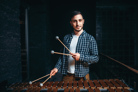 Young male xylophone player with sticks in hands