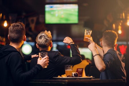 Three men watches football on TV in a sport bar Foto de archivo