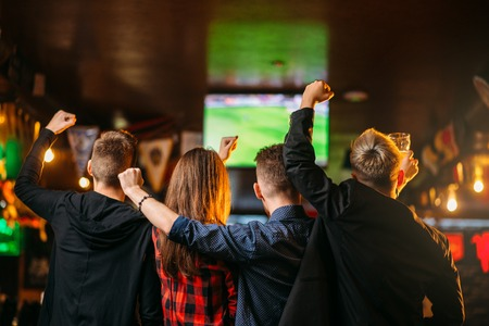 Friends watches football on TV in a sport bar Archivio Fotografico