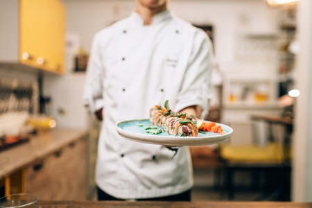 Male chef hold sushi rolls on plate, asian food