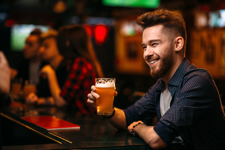 Man drinks beer at the bar counter in a sport pub