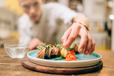 Male chef cooking sushi rolls, japanese food