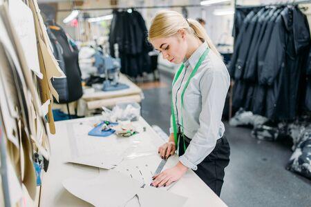 Designer de roupas mede um padrão, costura Foto de archivo