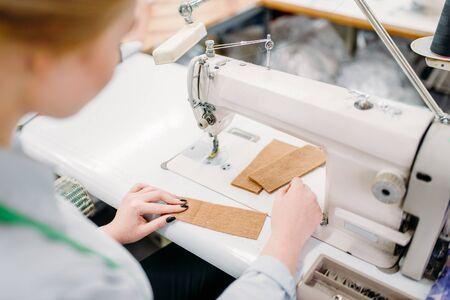Dressmaker sews fabrics on a sewing machine