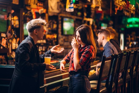 Young man talks with woman at the bar counter