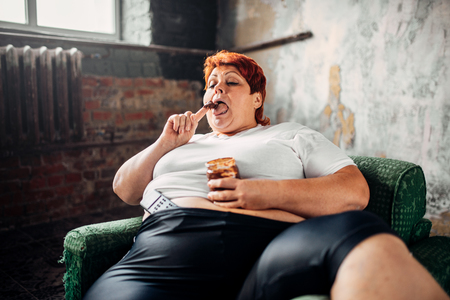 Overweight woman sits in a chair and eats sweets