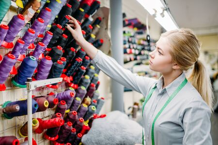 Clothes designer chooses color threads