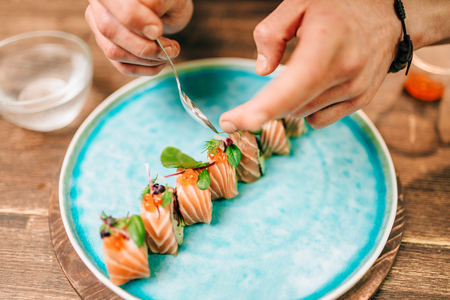 Male person cooking sushi rolls with salmon