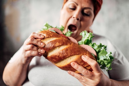 Fat woman eats sandwich, overweight and bulimic