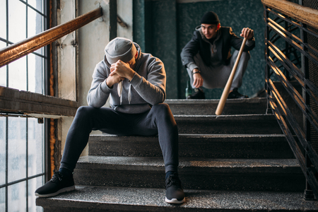 Two male gangsters are sitting on the stairs Stock Photo