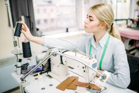 Female dressmaker sews on serger machine Stock Photo