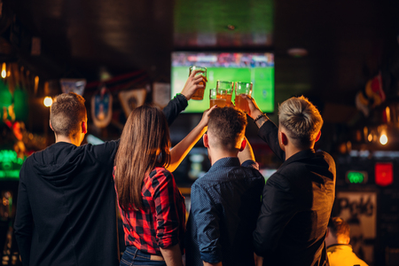 Friends watches football on television in a sport bar