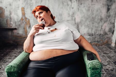 Overweight woman sits in chair and eats sweet cake