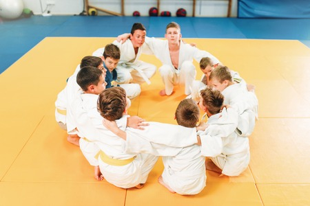 Boys in kimono sitting on the floor, judo training Banque d'images