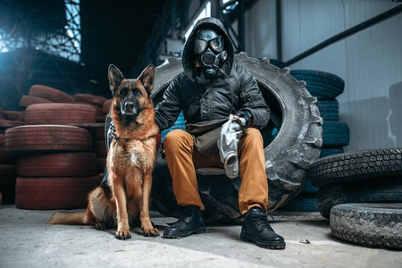 Stalker in gas mask and dog, post-apocalypse Stock Photo