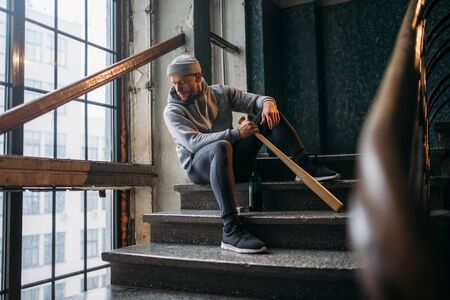 Male theif with baseball bat sits on stairs