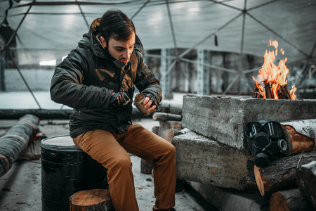 Stalker, male person eating against fireplace Stock Photo