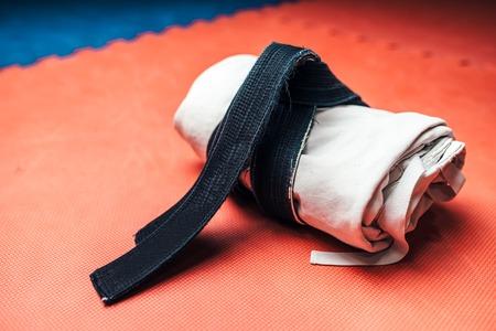 Martial arts, white kimono and black belt closeup Stock Photo