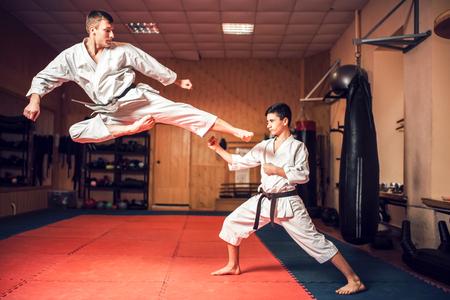 Martial arts masters practice kick in jump Foto de archivo