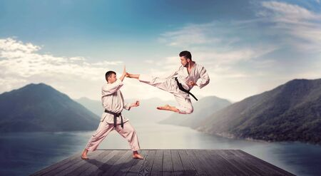 Martial arts, kick in jump, training on the pier Stock Photo
