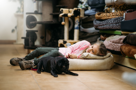 Little girl with puppy are sleep in pet shop