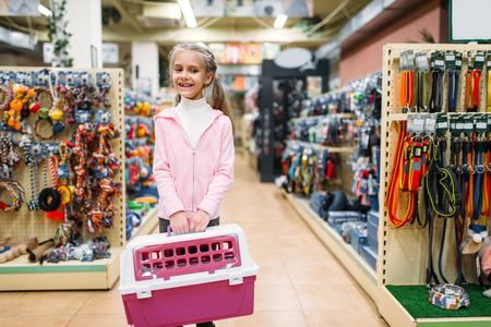 Happy little girl with carrier for cat in pet shop Stock Photo