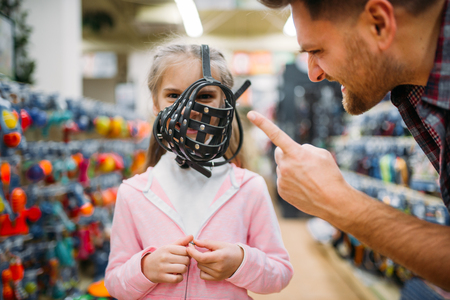 Pet shop, father and daughter chooses muzzle Stock Photo