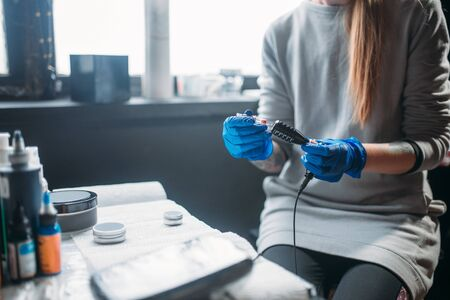 Female tattooer prepares tattoo machine in salon Stock Photo