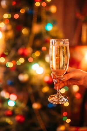Female hand holds glass with champagne, christmas