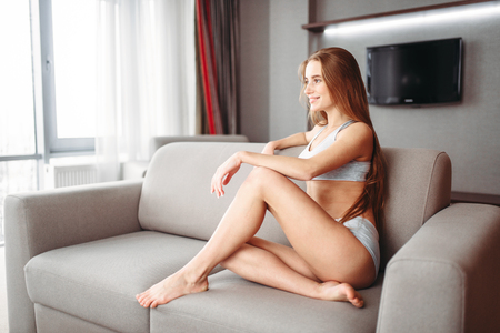 Young sexy woman in underwear sitting on the couch