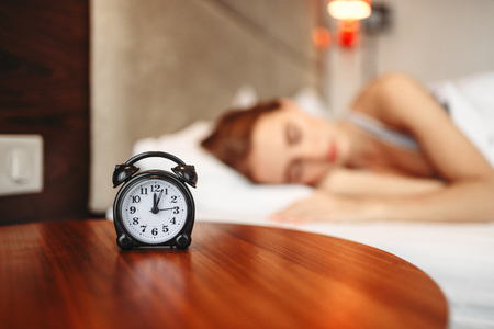 Alarm clock, woman covering her ears with pillow Stock Photo