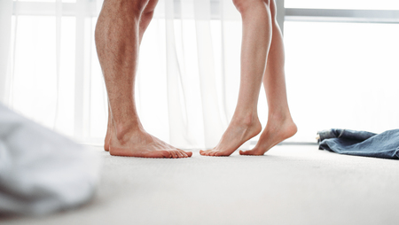 Male and female legs, intimate games in bedroom Stock Photo