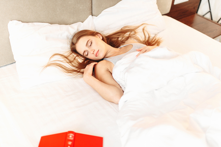 Beautiful woman with book sleeping in the bed Stock Photo
