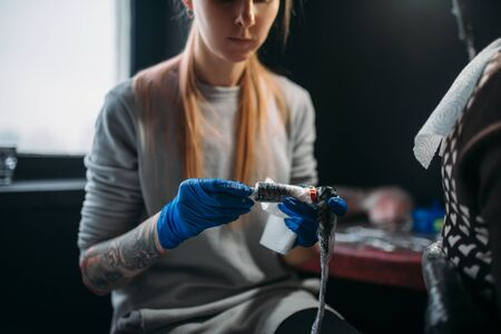 Female tattooist prepares tattoo machine Stock Photo