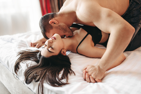 Sexy couple lying and kissing on big white bed Stock Photo
