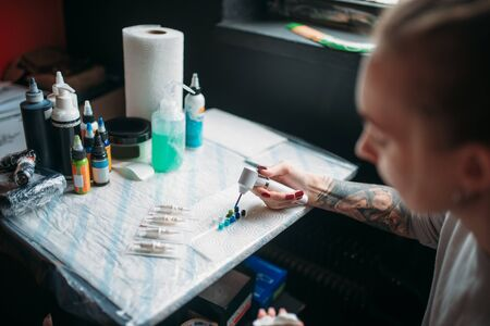 Female tattoo artist prepares color ink Stock Photo