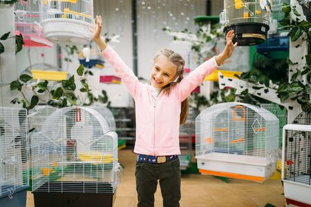 Little girl between cages for birds in pet shop Stock Photo