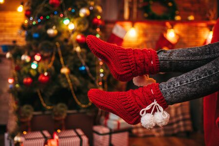 Female person feet in merry red socks, christmas Stock Photo