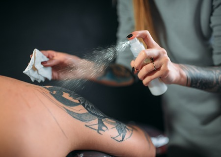 Tattoo master sprays the freezing on clients skin Stock Photo