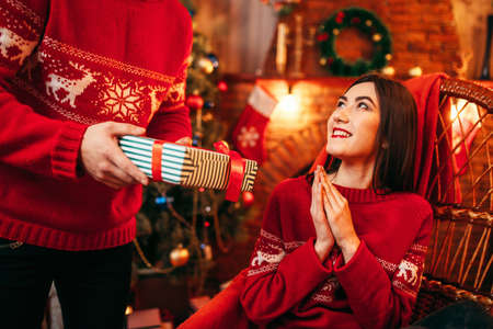 Xmas, male person makes gift to beautiful woman