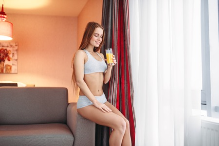 Woman in underwear drinking fresh orange juice