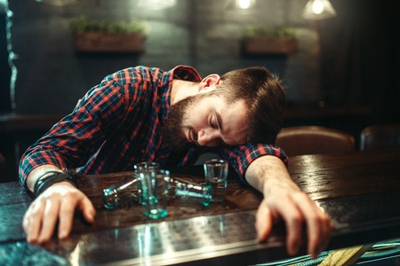 Drunk man sleeps at bar counter, alcohol addiction