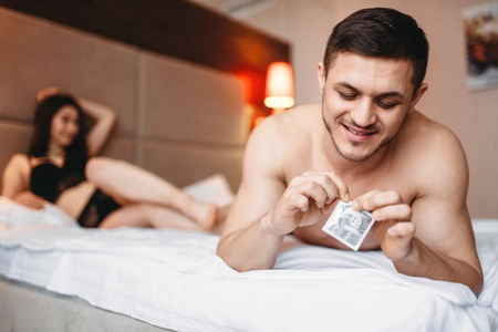 Couple lying in bed, man holds condom in his hand Stock Photo