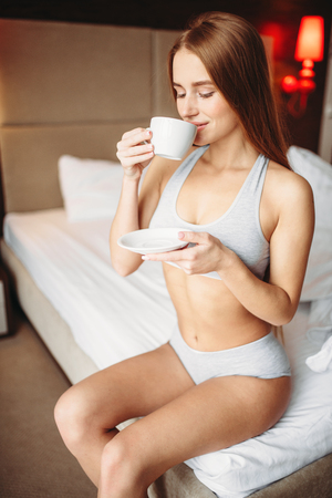 Beautiful woman drinks coffee in bed, good morning Stock Photo