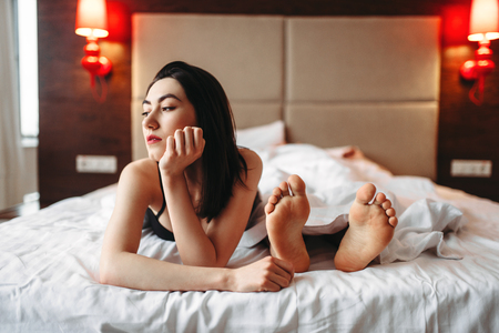 Woman in underwear lying in bed against male feet