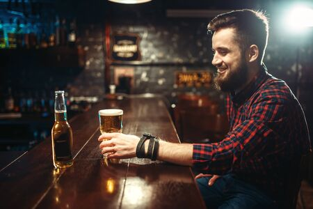 One bearded man drinks beer at the bar counter