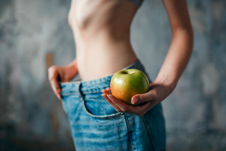 Woman with apple in hand tries on big size jeans Stock Photo