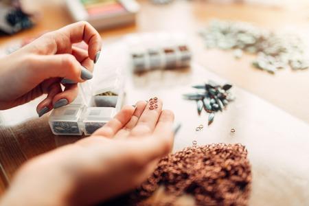 Female hands holds little metal rings, needlework