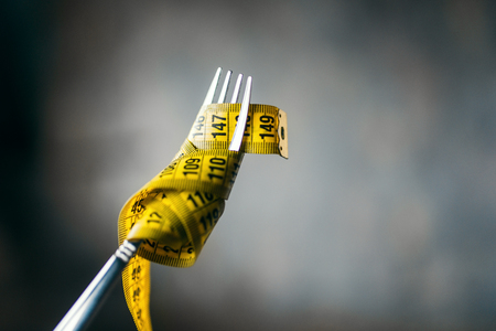 Measuring tape on a fork closeup, weight loss